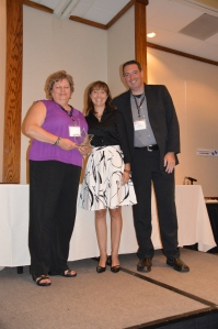 Noreen Rude of the City of Calgary receives the award from Maria DeBruijn, along with USA judge Joel Mills.